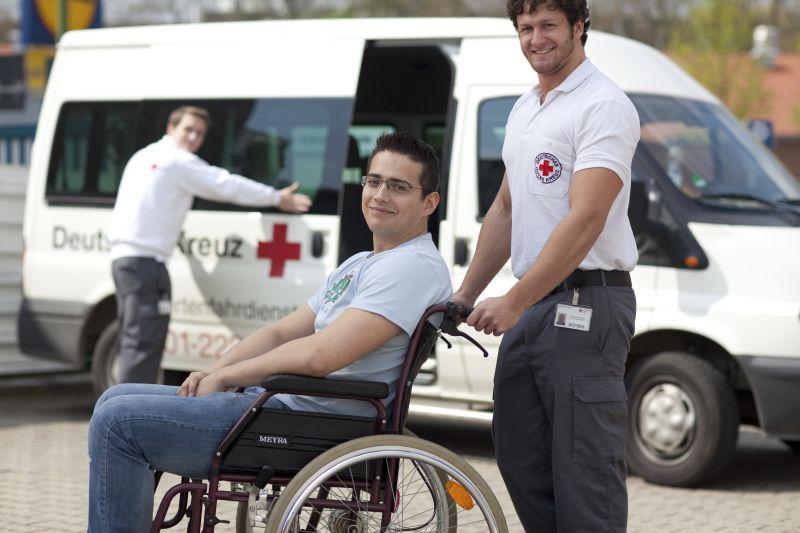 Fahrdienst für Behinderte: junger Mann im Rollstuhl und Helfer des DRK. - März 2010